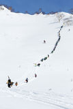 Skiers and snowboarders climbing the steep mountain for freeride. KAMCHATKA PENINSULA, RUSSIA - MARCH 9, 2014: Large group of sportsmens - skiers and Royalty Free Stock Images