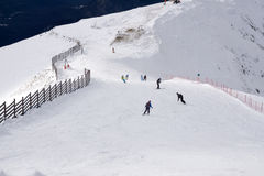 Skiers and snowboarders going down the slope Stock Photos