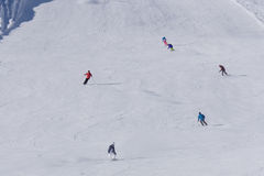 Skiers and snowboarders going down the slope Royalty Free Stock Photos