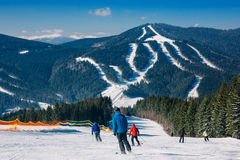 Skiers and snowboarders going down the slope at ski resort Stock Photo
