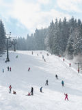 Skiers and snowboarders going down the slope Royalty Free Stock Image