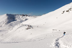 Skiers and snowboarders hike on the top of The Remarkables Royalty Free Stock Photography