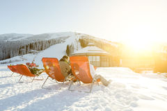 Skiers and snowboarders resting in chairs at Chopok downhill, Jasna - Slovakia. Skiers and snowboarders relaxing in chairs near apres ski bar at Chopok downhill Royalty Free Stock Image
