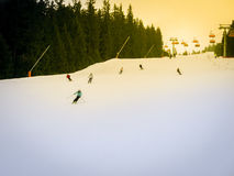 Skiers and snowboarders riding on a ski slope Stock Image
