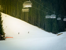 Skiers and snowboarders riding on a ski slope Stock Images