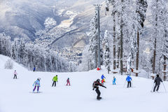 Skiers and snowboarders riding on a ski slope Royalty Free Stock Image
