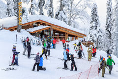 Skiers and snowboarders riding on a snowy ski slope Stock Photos