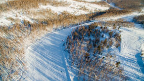 Skiers and snowboarders slide down mountainside near lake Bannoe. Aerial Royalty Free Stock Images
