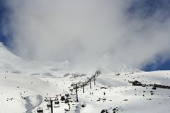 Skiers, snowboarders and tourists using the cable cars or ski lift to get to the top of a snow covered misty mountain stock photo