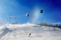 The skiers, snowborders and mountain rainbow in Jasna Low Tatras Stock Photography