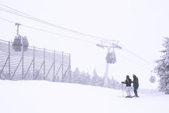 Skiers stands near the top of a ski mountain Royalty Free Stock Images