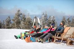 Skiers sunbathing in sunbed. Male and female skiers sunbathing in sunbed on ski terrain Stock Images