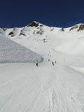Skiers take the piste down to a ski resort Stock Photos