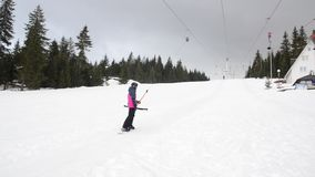 Skiers using ski lift anchor on the mountain. People moving slowly uphill on drag lift on snow covered landscape. Winter sports, s. Kiing, recreation and stock footage