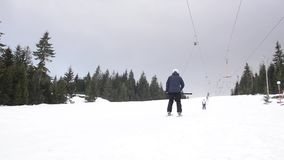 Skiers using ski lift anchor on the mountain. People moving slowly uphill on drag lift on snow covered landscape. Winter sports, s. Kiing, recreation and stock video footage