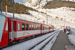 Skiers waiting for their train on Dieni train station in Switzer royalty free stock photography