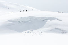 Skiers walking on snow covered mountain ranges Stock Photography
