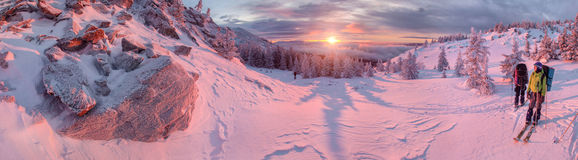 Skiers watching sunrise in winter mountains Royalty Free Stock Photos