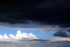 In the skies. Clouds on a blue skie just before the storm Stock Image