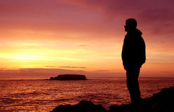 Skies The Limit. Man looking out over an ocean sunset stock photo
