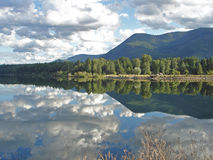 Skies reflected in Montana Lake. Cloud formations and mountain scenery are reflected in a Montana lake making for a beautiful mirror image royalty free stock photography