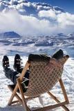Skieur aux montagnes d'hiver se reposant sur le soleil-canapé Photo stock