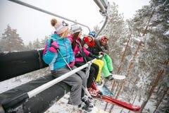 Skieur d'amis s'asseyant à l'ascenseur de chaise de ski dans le beau jour ensoleillé Photo stock