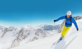 Skieur d'homme courant en descendant Image stock