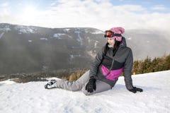 Skieur de fille se trouvant sur la neige sans ski, montagne Image stock