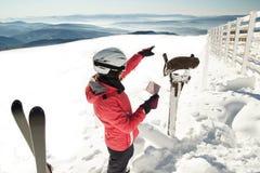Skieur de jeune femme à la station de sports d'hiver d'hiver en montagnes lisant la carte, trouvant le chemin Photographie stock