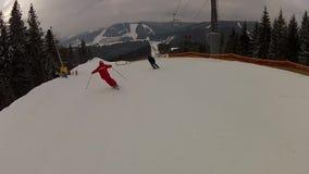 Skieur descendant la descente de ski dans Bukovel banque de vidéos