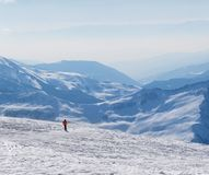 Skieur en descendant sur la pente et les montagnes hors-piste neigeuses en brume Photo stock