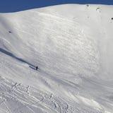 Skieur en descendant sur la pente neigeuse de ski pour le freeride Photographie stock libre de droits