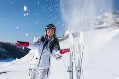 Skieur féminin espiègle jetant la neige en l'air dans l'air Photos libres de droits