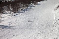 Skieur incliné sur la pente neigeuse de ski au jour d'hiver du soleil photo stock