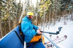 Skieur masculin à l'aide du bâton de selfie prenant des photos tout en skiant image libre de droits
