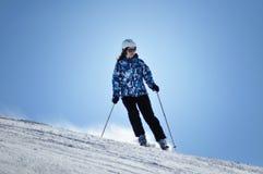 Skieur skiant en bas de la pente dans un beau jour ensoleillé Photographie stock libre de droits