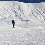 Skieur sur la pente dans le jour d'hiver du soleil Photos libres de droits
