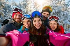 Skieurs d'amis des vacances d'hiver prenant la photo avec le téléphone portable Image stock