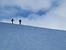 Skieurs dans la neige contre l'horizon Photo stock