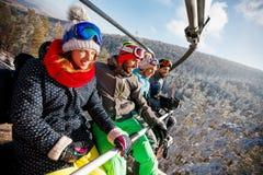 Skieurs et surfeurs d'amis sur le remonte-pente Photographie stock libre de droits