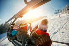 Skieurs et surfeurs d'amis sur le remonte-pente dans la montagne à W Image libre de droits