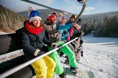 Skieurs et surfeurs de sourire d'amis sur le remonte-pente dans le bâti Photographie stock libre de droits