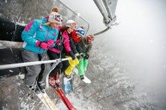 Skieurs et surfeurs heureux d'amis sur le remonte-pente pour skier dedans Photo stock