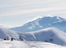 Skieurs et surfeurs sur la route neigeuse avant incliné sur des off-pis images stock