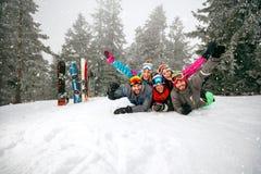 Skieurs gais se trouvant sur la neige et ayant l'amusement Image libre de droits