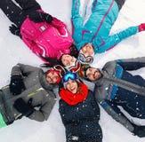 Skieurs gais se trouvant sur la neige et ayant le point de vue supérieur d'amusement Images libres de droits