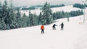 Skieurs méconnaissables de montagne sur la pente alpine de ski Photographie stock