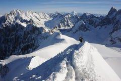Skieurs marchant sur l'arête de montagne couverte de neige dans les Alpes français en hiver avec le beau panorama et le ciel bleu Images stock