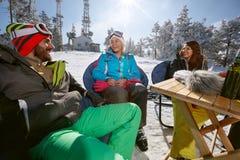 Skieurs masculins et féminins parlant et souriant en café sur le terrai de ski Photographie stock libre de droits